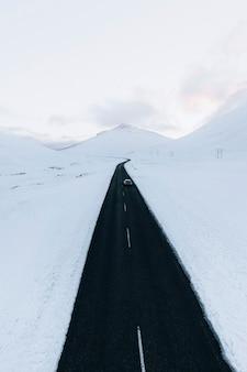하얀 겨울 풍경을 가로지르는 긴 검은 길