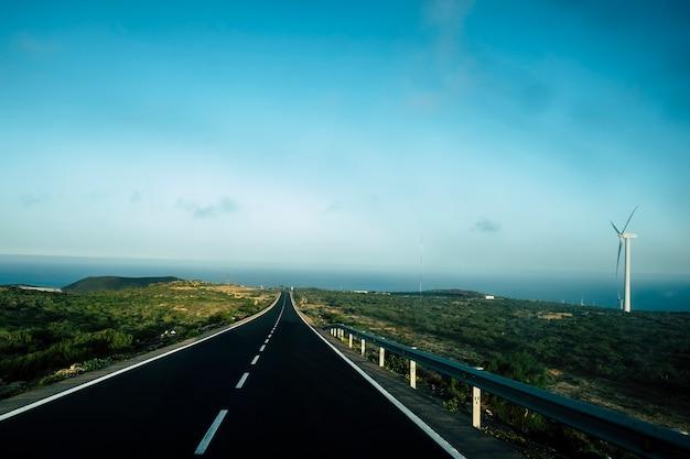 Длинная черная дорога с белыми полосами посередине, ведущая к океану. ветряная мельница справа и удивительная природа вокруг. путешествовать и открывать концепции в прекрасном мире