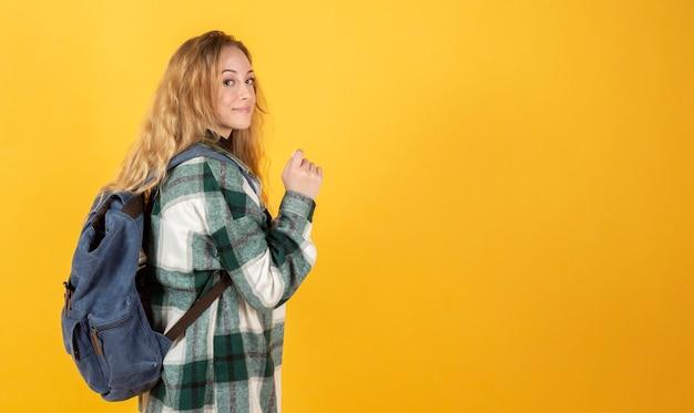 Женщина с длинными светлыми волосами, с рюкзаком, желтый фон, концепция путешествия, копия пространства