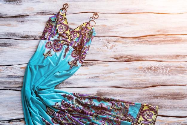 프린트가 있는 롱 블루 드레스. 흰색 나무 배경에 드레스. 쇼케이스에 세련된 패턴 의류. 새 컬렉션의 마지막 항목입니다.
