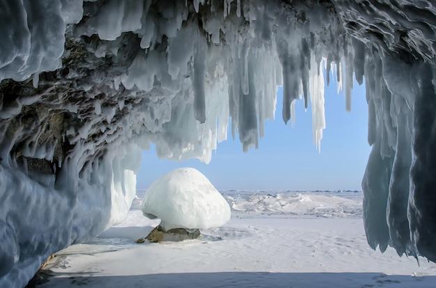 海岸の崖の氷の洞窟にある長い青い氷柱。