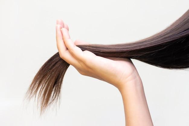 手のひらに長い茶色の髪、ヘアケア