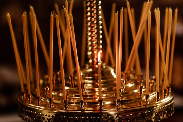Long candles group in orthodox church.