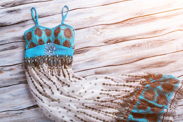 프린트가 있는 캐주얼 롱 드레스. 나무 배경에 여름 드레스입니다. 햇빛 아래에서 의류와 함께 쇼케이스. 트렌디한 옷을 저렴한 가격에.