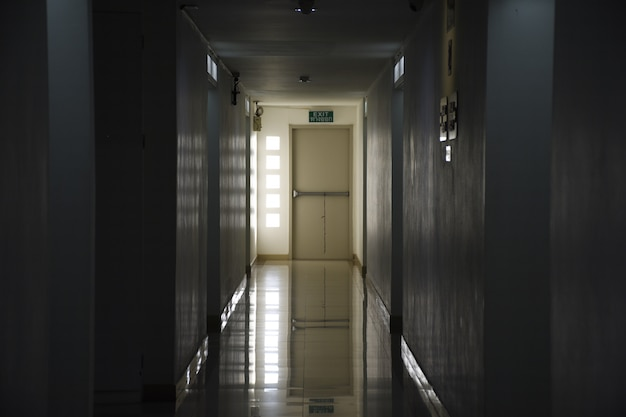 The long corridor in the building goes to the exit at night.