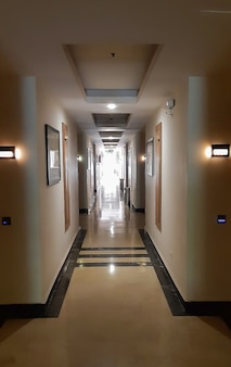 Длинный коридор, ведущий в перспективу, ряд комнат по бокам, яркий свет в конце. все освещено лампами