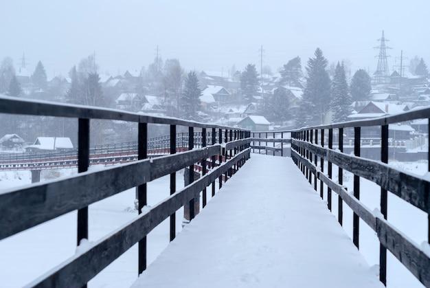 Длинный изогнутый заснеженный мост с деревянными перилами через реку в зимней сельской местности