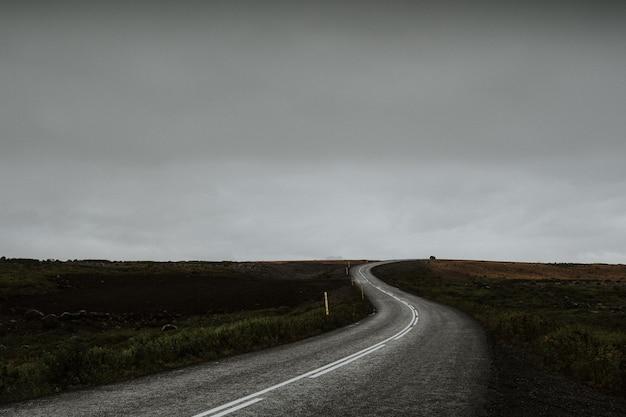 アイスランドの緑のフィールドの真ん中にある曲がりくねった長い道