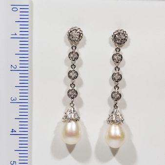 Long designer gold earring with pearls and diamonds on a white background next to the ruler