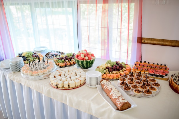 Long dinner table served with sliced fruits and different kinds of bakery