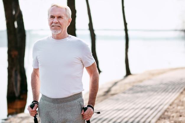 Дисциплина на дальней дистанции. уверенный зрелый мужчина практикует спортивную ходьбу в парке, глядя прямо
