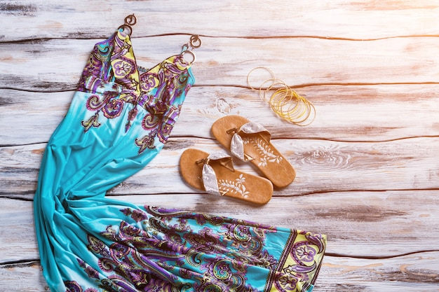Long dress and flip flops. blue dress and brown footwear. showcase with clothes under sunlight. stylish female clothing on sale.