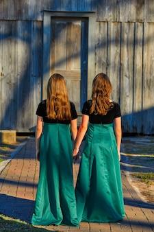 Long dress twin teen sisters hand in hand