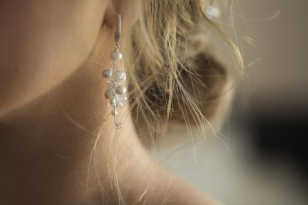 보라색 보석이 달린 긴 귀걸이가 여성의 귀에 매달려 있습니다.