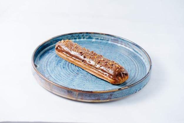 Длинный эклер с топленым шоколадом и орехами