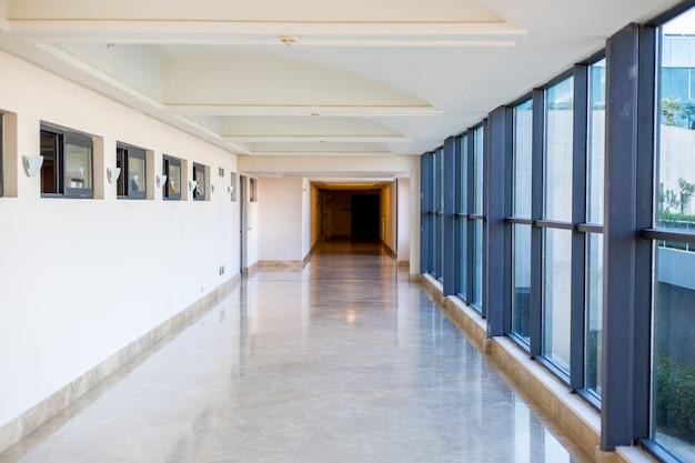 大きなガラス窓のある長い空の廊下。モダンな廊下。商業建築