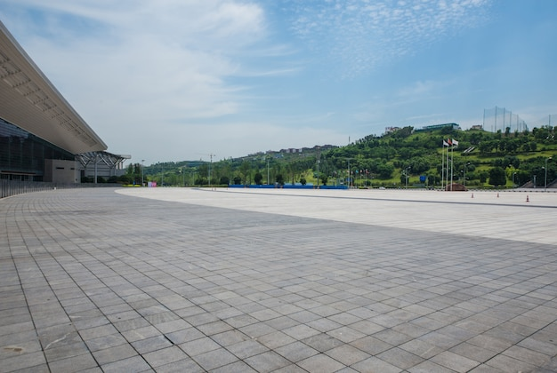 Long empty footpath in modern city square with skyline