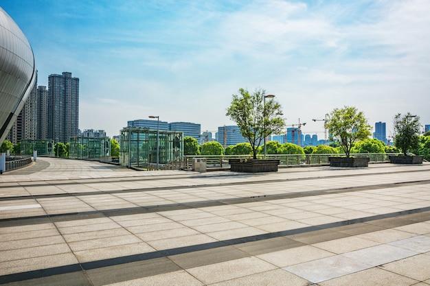 Lunga sentiero vuoto nella piazza moderna della città con skyline.