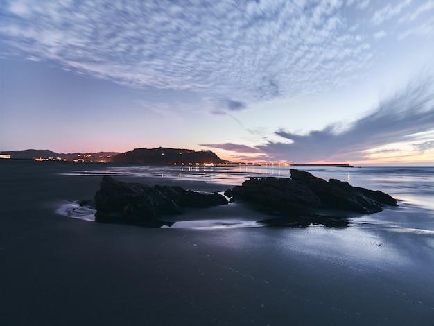 Долгая выдержка после захода солнца с 2 утесами на переднем плане с светами прибрежной деревни и своего маяка на заднем плане.