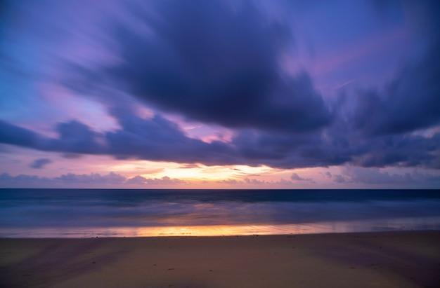 긴 노출 다채로운 하늘 일몰 또는 일출 다채로운 하늘 레코딩 및 모래 해안에 부서 지는 빛나는 파도 바다 표면에 아름 다운 빛 반사 놀라운 풍경 또는 바다 자연 배경입니다.