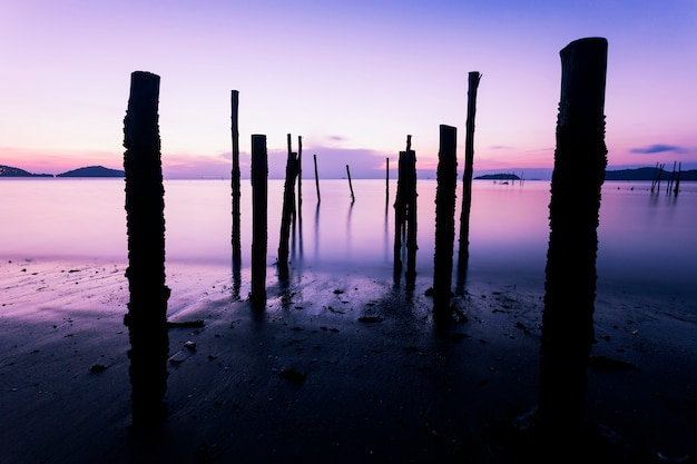 Long exposure image of dramatic sky seascape with old wooden pole in the sea sunset