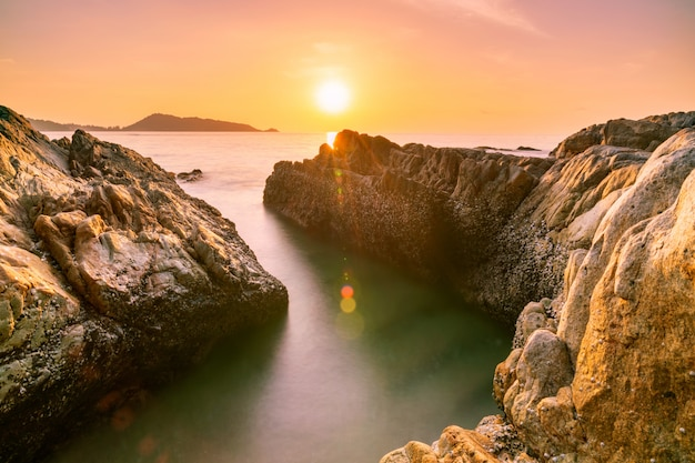 Long exposure image of dramatic sky seascape with rock in sunset scenery
