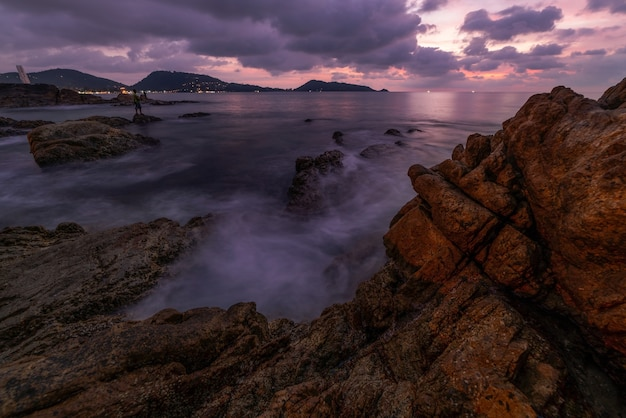 Long exposure image of dramatic sky seascape with rocks in the foreground sunset or sunrise over sea scenery background.