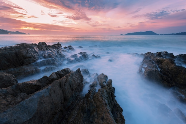 Long exposure image of dramatic sky and wave seascape with rock