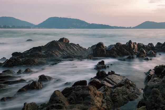 일몰 풍경에 바위와 극적인 하늘과 파도 바다의 긴 노출 이미지