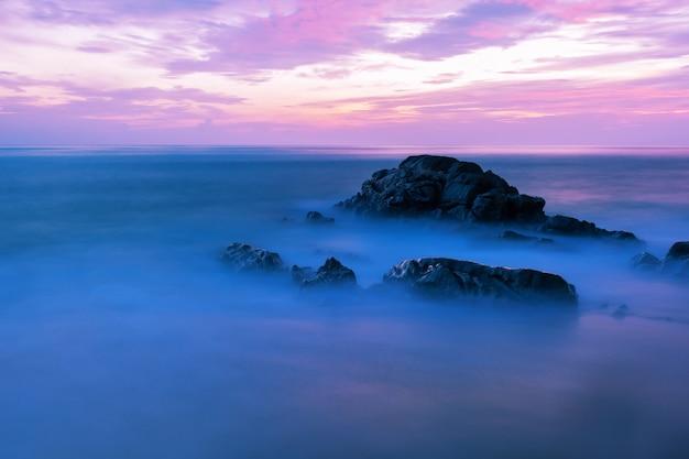 바위와 극적인 하늘과 파도 바다의 긴 노출 이미지