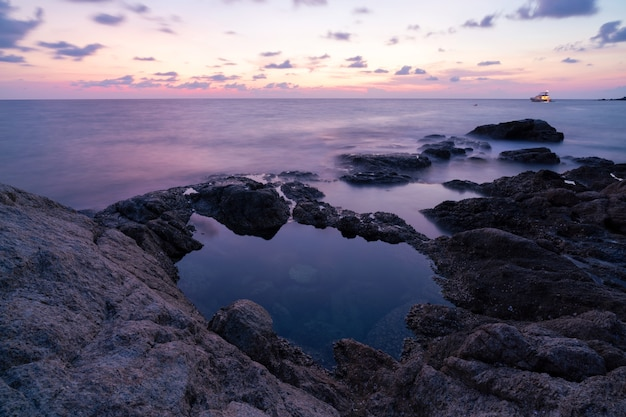 夕日や日の出の風景の中の岩と劇的な空の海の長時間露光画像