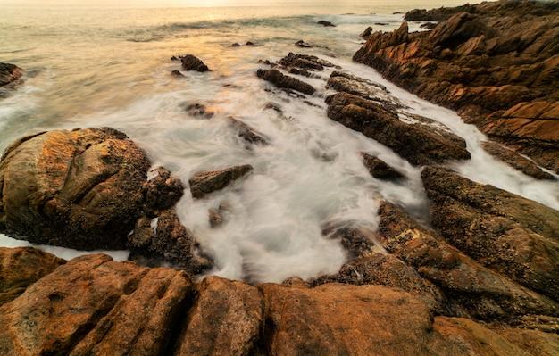 前景の日没または海の風景の背景の日の出に岩がある劇的な空の海の風景の長時間露光画像。