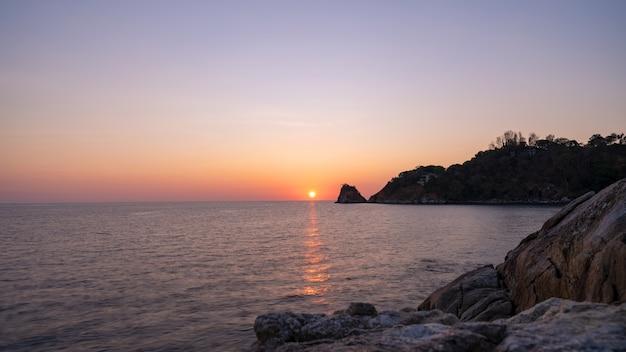 フォアグラウンドの日没の風景の風景の中の岩と劇的な空の海の長時間露光画像。
