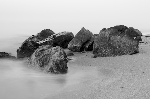 Фото ландшафта долгой выдержки скалистого побережья в рассвете.