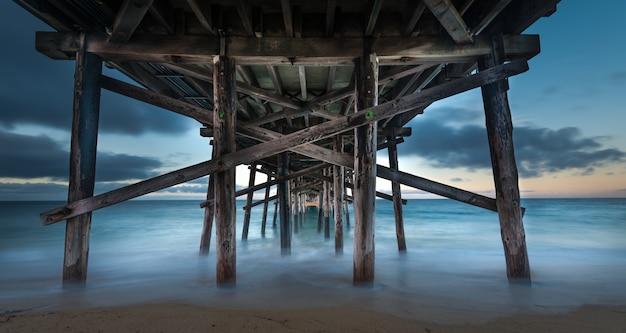 Lunga esposizione della parte inferiore di un molo di legno in mare in california la sera
