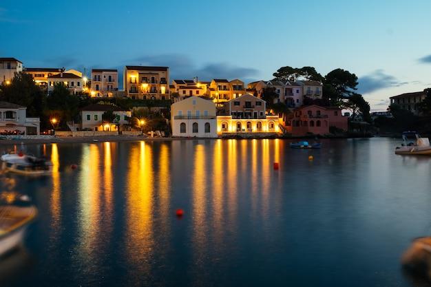 湾にボートが沈む夕日の海辺のかわいい旧市街の長時間露光。