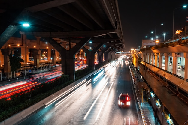 Long exposure photography showing light tracffic on highway in the city.