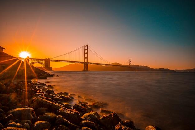 長時間露光サンフランシスコのゴールデンゲートで赤い夕日が橋の上に太陽が隠れています。アメリカ