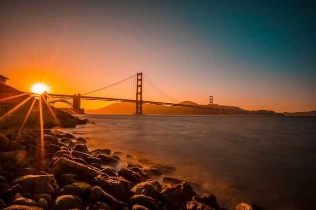 Long exposure red sunset at the golden gate of san francisco with the sun hiding on the bridge. united states