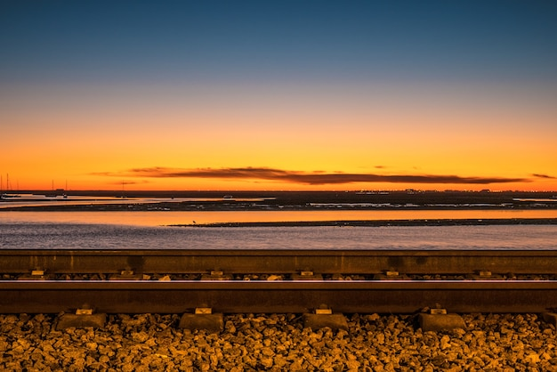 Снимок с длинной выдержкой железной дороги фаро на закате и море.