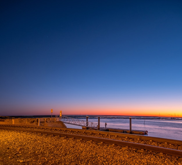 Снимок с длинной выдержкой железной дороги фарос на закате и море.