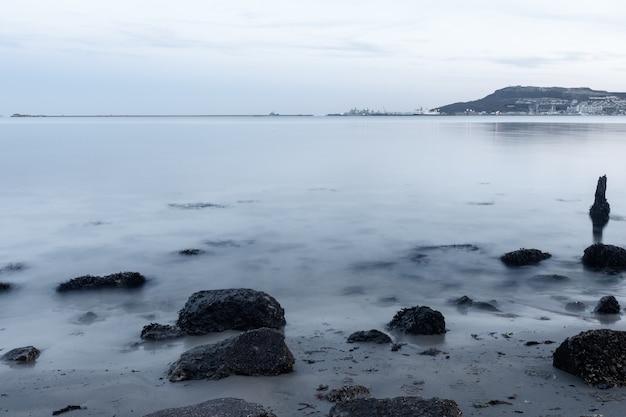 ポートランド、ウェイマス、ドーセット、イギリスの近くの海岸にある石の長時間露光ショット
