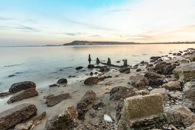 英国ドーセット州ウェイマスのポートランド近くの海岸にある石の長時間露光ショット