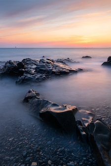 Long exposure shot of the seascape in guernsey during a sunset