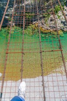 Long extreme suspension iron bridge across the river moraca. montenegro.