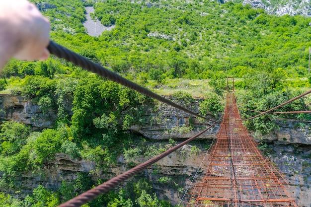 モラカ川を渡る長い極端なサスペンション鉄橋。モンテネグロ。