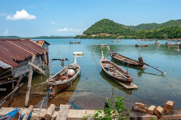 古いさびた屋根の水の中の高床式の小屋の隣の水上でのタイの長い漁船