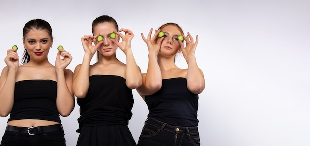 Long format women in black tops fooling around making eye mask with slices of cucumber beauty