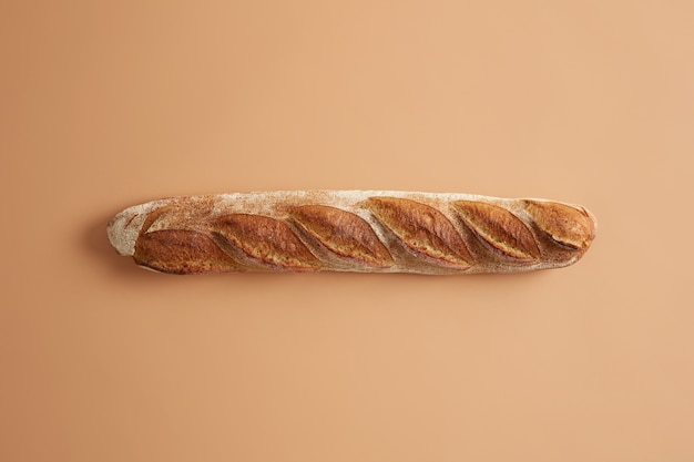 Long french baguette with crispy golden crust isolated on beige studio background. freshly baked type of bread for tasty nutrition. overhead shot. tasty gourmet product baked on bakery. food concept