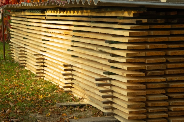 Длинные свежие доски осенью лежат плоскими стопками на улице. выборочный фокус.